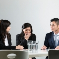 Chinese businesswoman yawning during business meeting